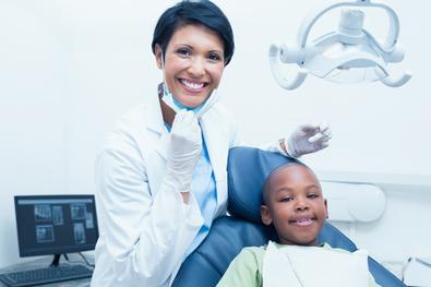 Smiling female hygienist examining boy's teeth