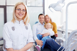 Family in dentist's office with dental professional smiling in foreground