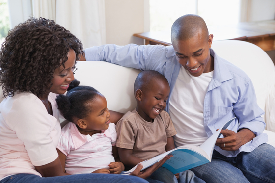 Happy African American family sitting on couch together reading a book