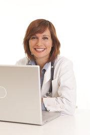 Portrait of smiling young female doctor in white coat sitting at laptop