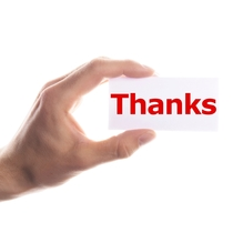"Hand holds small white card that simply has ""Thanks"" written in red on it"