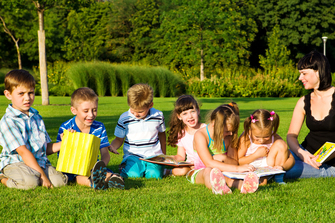Children and teacher reading outside