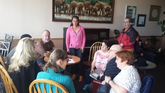 Senator Riley meeting with constituents at a coffee shop in Forest Grove