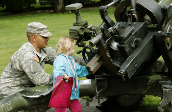 A soldier shows a little girl artillery.