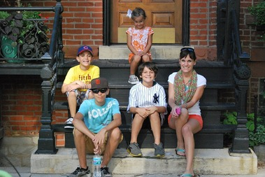 A happy family sets on the front steps of their home.