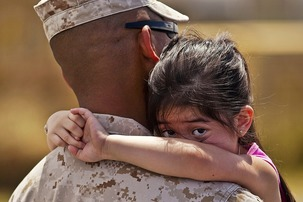 A soldier hugs his little daughter.