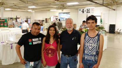 Sen. Riley with 3 young people in front of a 4H exhibit