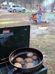 camp stove and burgers with family in background
