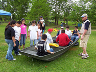 volunteer with kids sitting in boat on land