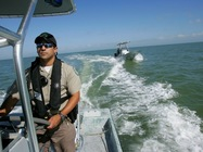 officer on offshore boat in cap and gear