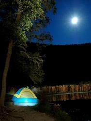 moon, dark sky with lighted tent below