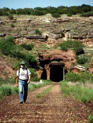 hiker on Caprock rails trail, exiting tunnel