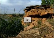 Red cliffs on right with water, trees and sky