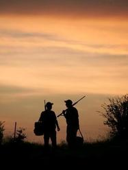 two hunters silouetted at sunset