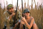 man and woman in grasses, shotguns