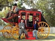 red stagecoach, picket fence, people in costume