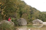 adult, child sit on boulder above woodsy creek