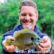 happy man holding hand-sized fish