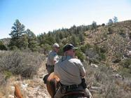 two game wardens on horseback, rugged terrain