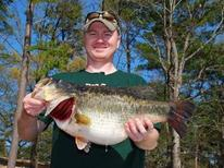 happy man holding big largemouth bass, pine forest