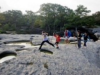 family, kids jumping across rocks, pools of water