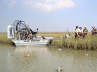 two wardens, duck hunters, sky, marsh, water with boat