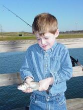 kid with two-fisted hold on a trout