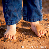 child's bare feet, jean cuffs, dirt