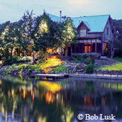 pond by house, reflecting lights at dusk