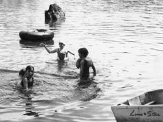 Black/white pic: kids swimming by row boat
