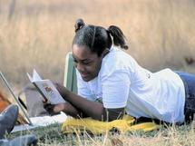 young girl reading in grass