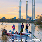 3 men lak fishing, power plant towers behind