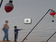 close up of fishing bobber, anglers in background