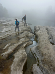man, 2 kids explore a foggy creek