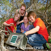 kids look into a geocache treasure box