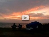 sillouette, 2 people, tent on beach, sunset