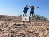 two girls standing on rocky hilltop