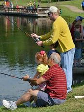 adults and child fishing at pond
