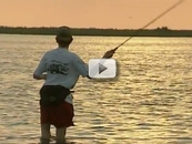 man casting in shallow bay water, sunset