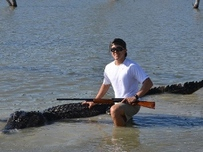 young hunter with 14 foot alligator in water