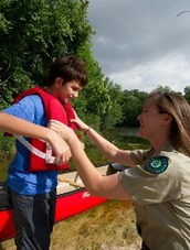 Park ranger helps child with safety vest