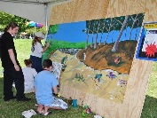 kids painting mural under a tent