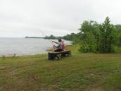 2 adults fishing along trail next to lake