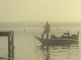 angler standing in boat, foggy morning