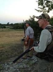 two watchful dove hunters in field