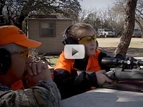 young hunter with mentor takes aim
