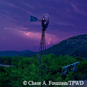 hillside, dark sky, lightening, windmill