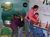 children and woman looking at exhibits
