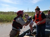 warden helps infant and mother from boat