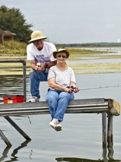 couple fishing on lake pier
